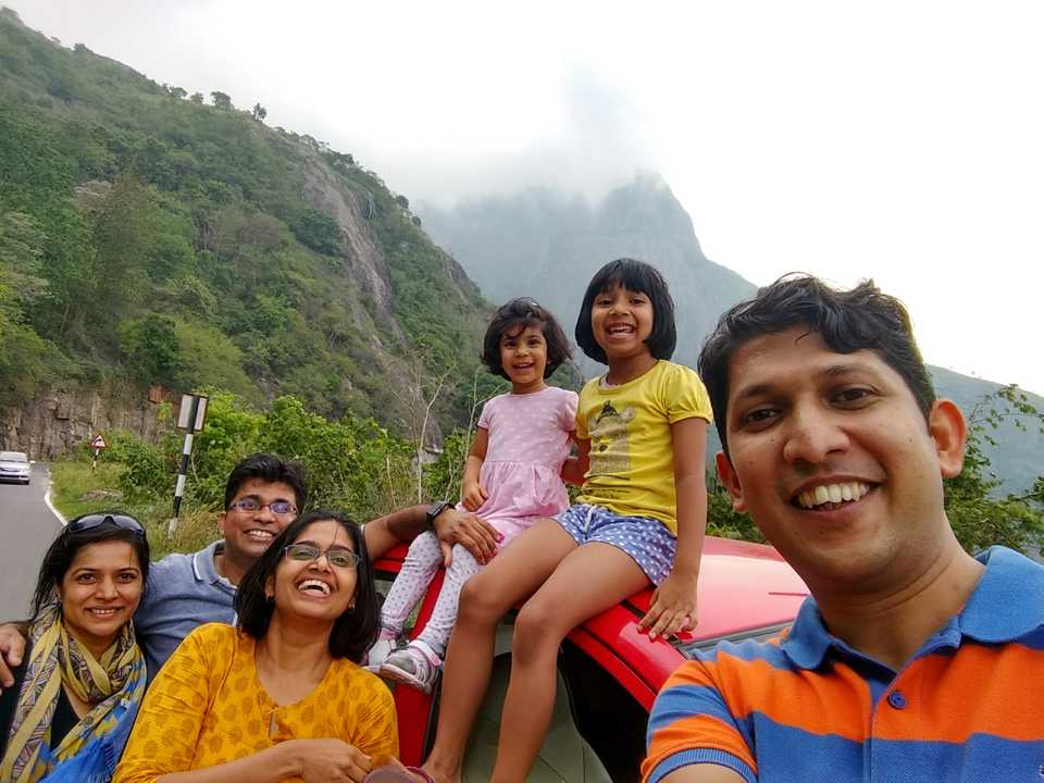 Smiling travelers in front of the Western Ghat mountains